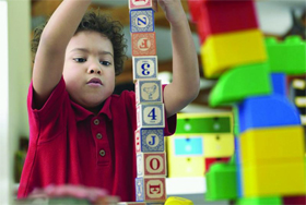 photo of boy building block tower