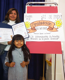 A parent graduate poses with her daughter during a graduation ceremony for the Abriendo Puertas/Opening Doors program.