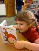 A young girl reads at the Tools of the Mind program.